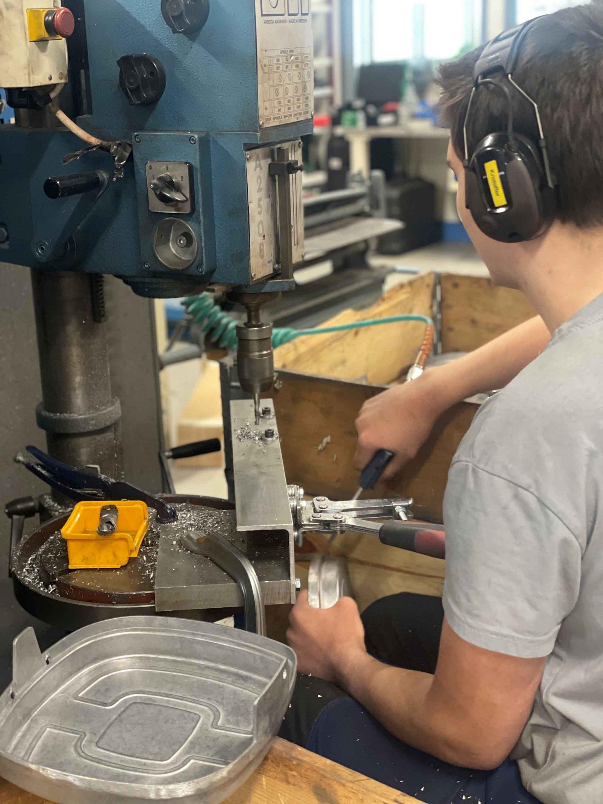 En mann som sitter å jobber med et boremaskin. Bilde